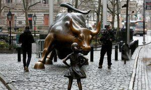 Una escultura de bronce de una niña sin miedo con los brazos en jarras plantando cara al toro de Wall Street